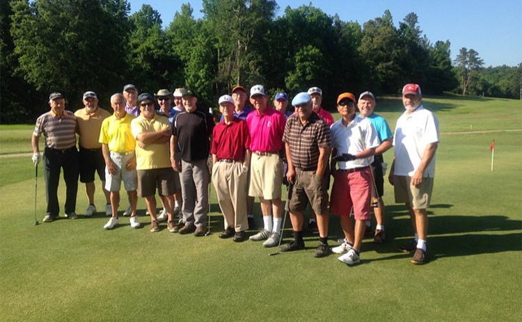 A group of golfers pose for a picture on the course at Paschal Golf Club